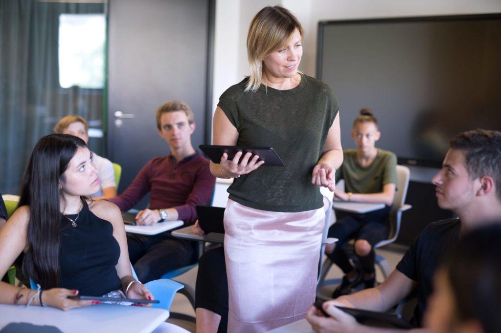 photo d'un professeur dans sa classe avec ses élèves ayant dans les mains une tablette EdTech